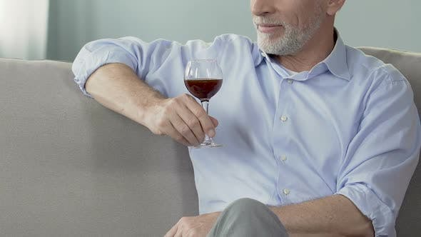 Elderly man sitting on sofa with glass of wine, enjoying moment, private winery