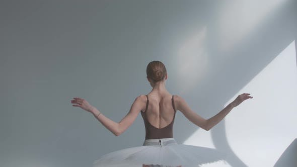 Fragile Ballerina on a White Background Standing with Her Back Performs Smooth Movements with Her