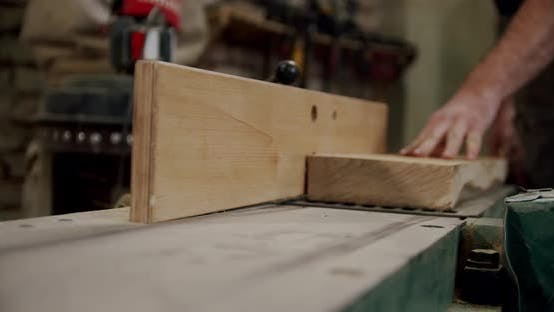 Thumbnail for Worker in a Woodworking Workshop Takes a Board and Puts It on a Machine in Woodworking Workshop of a