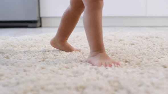 Thumbnail for Bare Legs of Unrecognizable Toddler Learning to Walk on Carpet