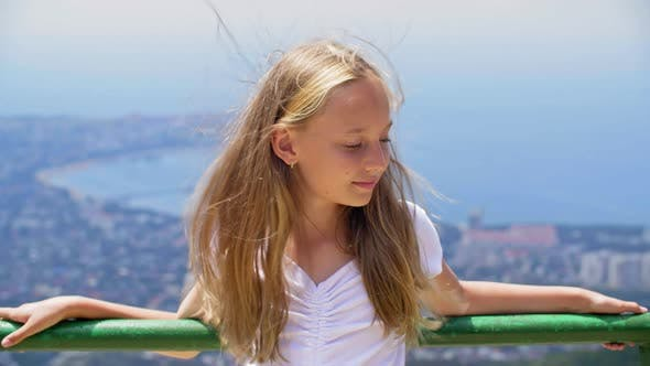Thumbnail for Smiling Girl Teenager with Hair on Wind Standing on Observation Deck on Mountain Peak Holding