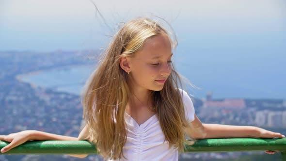 Thumbnail for Lächelnde Mädchen Teenager mit Haaren auf Wind stehend auf Aussichtsplattform auf Mountain Peak Holding