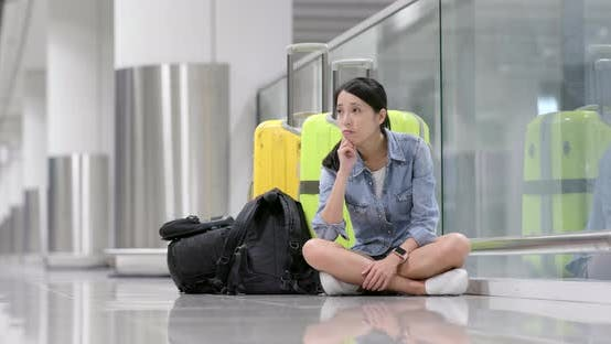 Thumbnail for Woman feeling bored and waiting for flight in airport with her luggage and backpack