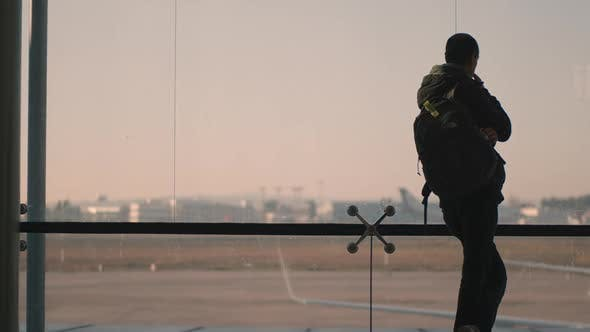 A Backview of a Man Standing Next To a Huge Airport Window