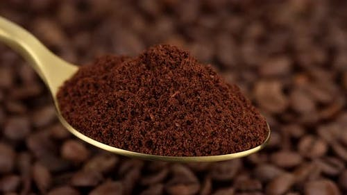 coffee. ground coffee in golden spoon and coffee beans on background rotate
