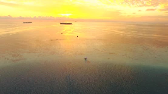 Thumbnail for Aerial drone view of a man and woman having dinner on a floating raft boat at sunset