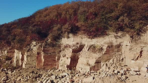 View of a large sand quarry with stones and forest. Camera motion left