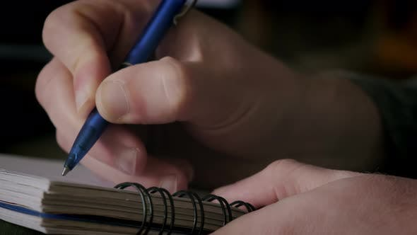 Close Up Futage of Man Writing Notes in Notebook