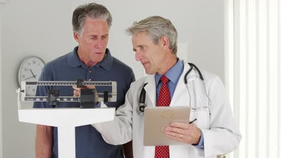 Thumbnail for Senior doctor weighing elderly patient
