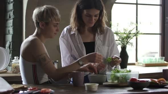 Cover Image for Glückliches Homosexuelles Paar macht Gemüsesalat und spricht am Tisch in der Küche. Spbd