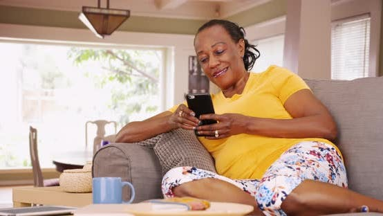 Thumbnail for An older African American woman uses her mobile phone while sitting on her couch
