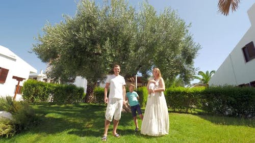 Young family with two children near olive tree in the garden