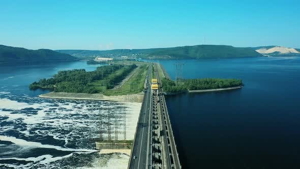 Thumbnail for View From a Quadcopter To the Road Bridge Over the River Dam. Cars Go Over the Bridge Over the River