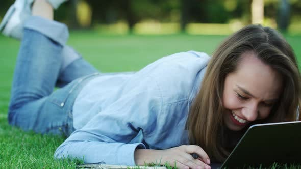 Thumbnail for Happy Woman Laughing While Using Laptop Computer on Green Lawn in Summer Park