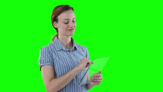 Caucasian woman holding a transparent screen on green background