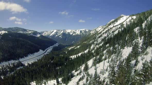 Thumbnail for Snowy Mountain Highway Aerial With Green Forest Valley Trees On Sunny Day