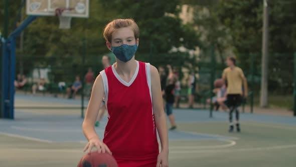 Porträt eines Mädchens in einer Schutzmaske, die mit einem Basketball auf dem Spielplatz der Stadt trainiert.  Ein