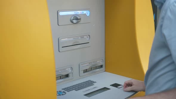 Close Up of Man's Hand Insert ATM Card Into Automated Teller Machine (Automatic Banking Machine) To