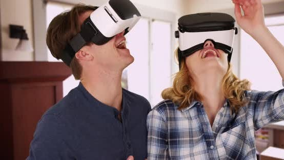 Thumbnail for Portrait of two friends using VR headsets at home, looking around and pointing