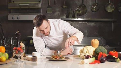 Chef Decorates Salad in Kitchen. Professional Chef Decorates Salad in Workplace.