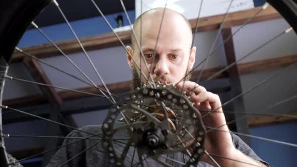 Thumbnail for Man fixing a bike wheel