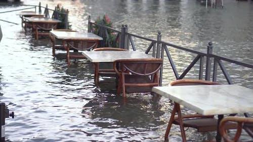 Restauranttische in einer mit Wasser überfluteten Stadt