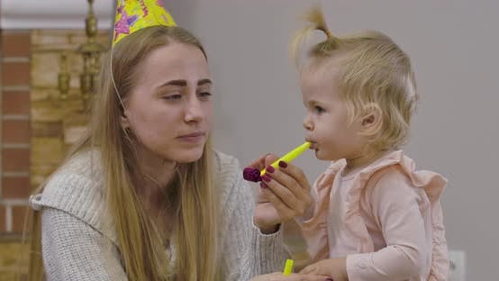 Close-up Portrait of Beautiful Caucasian Woman and Little Cute Girl Playing with Party Whistles at