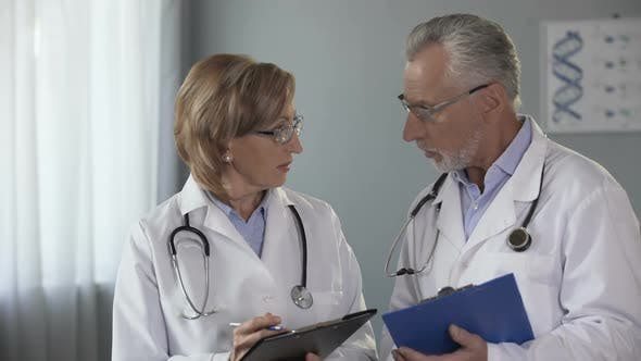 Thumbnail for Experienced Male and Female Doctors Comparing Results, Consulting on Diagnosis