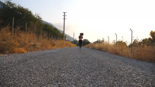 Healthy Girl Jogging Through Country Road and Listening Music on His Smartphone