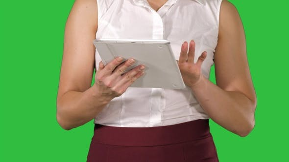 Thumbnail for Woman holding digital tablet and using it while walking