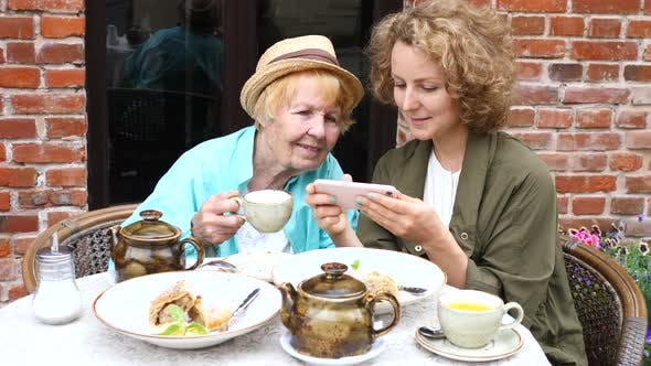 Thumbnail for Granddaughter Teaching Grandma How To Use Smartphone In Cafe