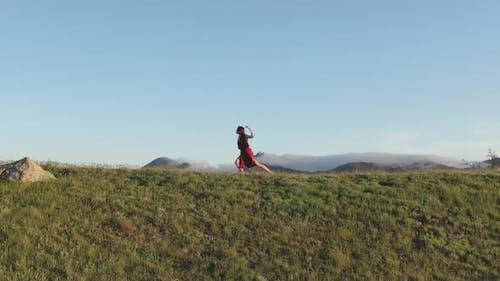 Ein Lichttanz, der von einer jungen Zauberin in einem roten Kleid auf einem Hügel in den Strahlen des