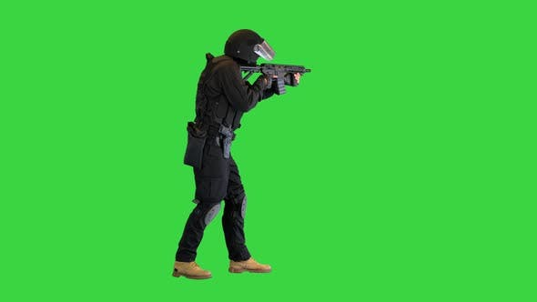 Police Operator with Assault Rifle Black Uniforms Aiming and Shooting on a Green Screen Chroma Key