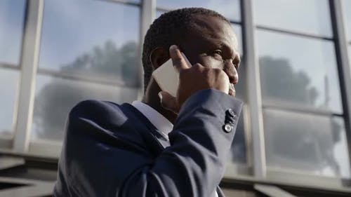 African black businessman on the street talking with smartphone