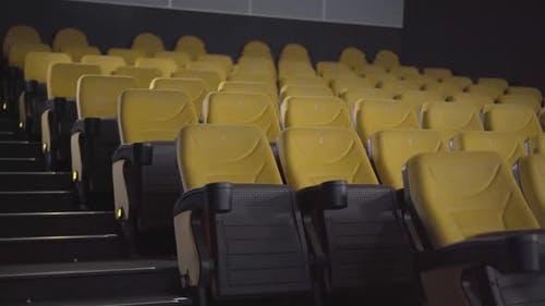 Wide Shot of Empty Cinema Hall with Rows of Yellow Chairs. No People in Movie Theatre. Luxurious