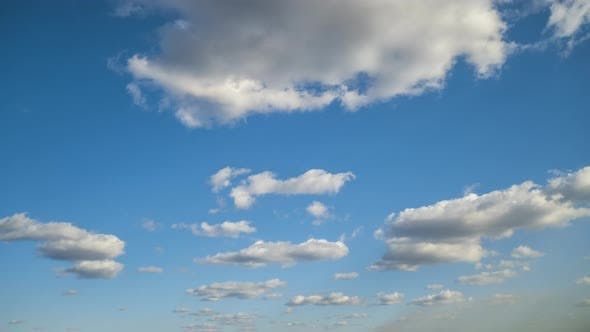 Time lapse footage of fast moving white clouds on blue clear sky.