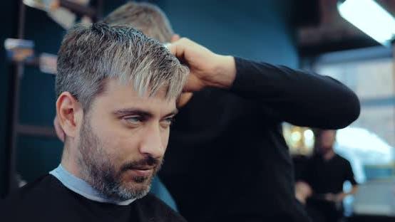 Nice Man with Gray Hair Makes a Haircut Stylist. Brutal Men's Salon. Portrait View