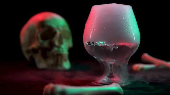 Thumbnail for Cognac Glassful with the Effect of Dry Ice Against the Skull and Bones on a Black Background. Slow