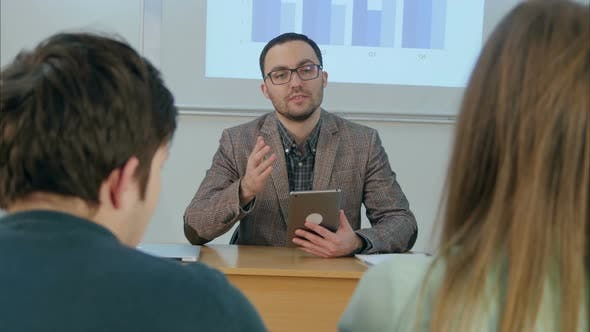 Thumbnail for Male Teacher Holding a Tablet Sitting in Front of Class