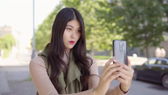 Young Asian Woman Takes Selfies Smartphone  Apartment Building Complex Background