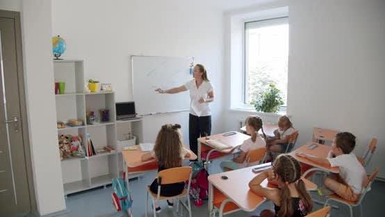 Children in Class the Teacher Explains on the Board