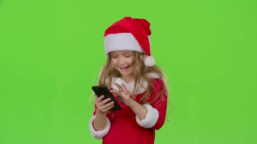 Kid Girl in an Embrace Photographed on a Smartphone. Green Screen