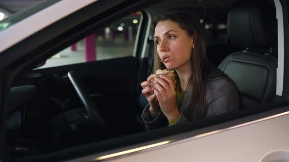 Woman Eating Sandwich Sitting in the Car on the Parking
