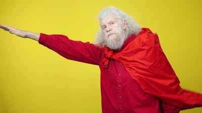 Senior Bearded Handsome Man Posing As Superman with Stretched Hand and Red Cloak