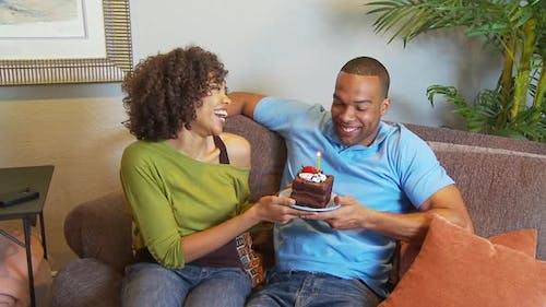 Couple with birthday cake blowing out candle