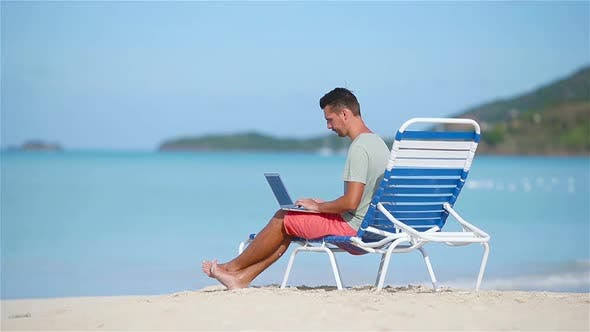 Thumbnail for Young Man with Laptop on Tropical Caribbean Beach. Man Sitting on the Sunbed with Computer and