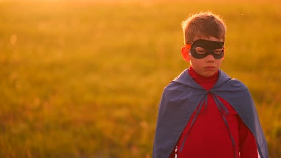 Thumbnail for A Child in the Costume of a Superhero in a Red Cloak Runs Across the Green Lawn Against the Backdrop