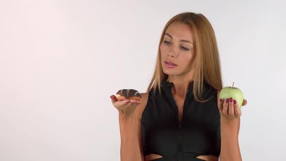 Thumbnail for Gorgeous Woman Choosing Between Apple and Chocolate Donut