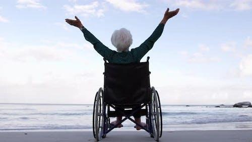 Frau mit ausgestreckten Armen auf Rollstuhl am Strand