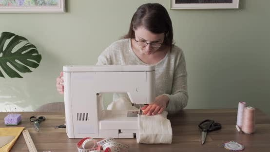Thumbnail for Adult Woman Sews on a Sewing Machine Sitting at Home at Table